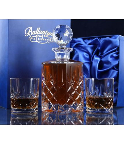 A fully cut whisky crystal hosting set consisting of a decanter and two tumblers. The set is presented inside a dark blue satin lined presentation box.