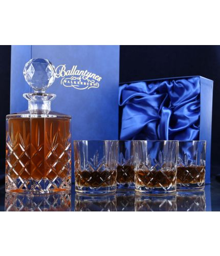 A fully cut whisky crystal hosting set consisting of a whisky decanter and four tumblers. The set is presented inside a dark blue satin lined presentation box.