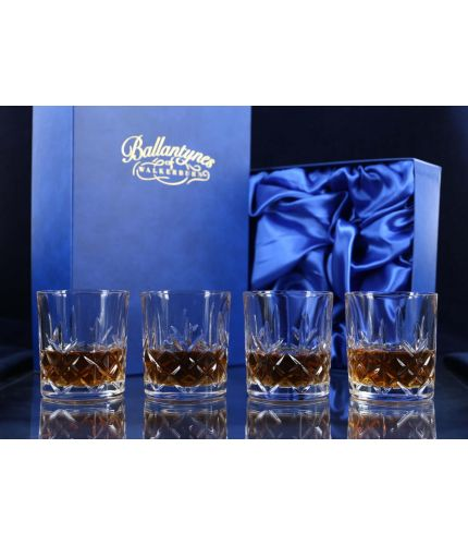 A fully cut whisky crystal hosting set consisting of four tumblers. The set is presented inside a dark blue satin lined presentation box.