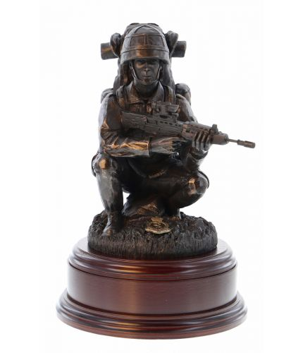 "A cold cast bronze resin statuette of a British Army Soldier crouching down  in full ""Marching Order"" We include this wooden base, a free badging service and an engraved brass plate as standard."