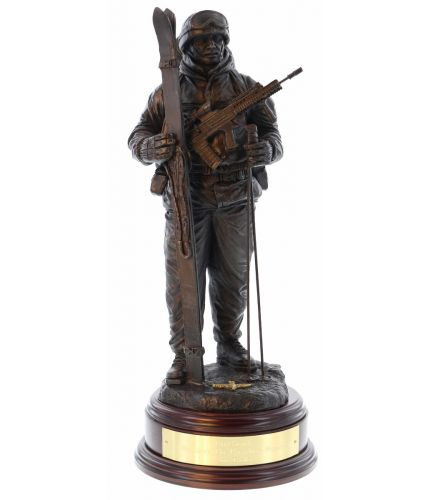 "12"" scale cold cast bronze resin sculpture of a British Army soldier dressed for arctic warfare with Skis and poles. His SA80 with ACOG is slung across his chest. We include this wooden base and an engraved brass plate as standard."
