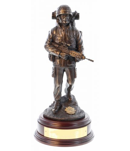 "A cold cast bronze resin statuette of a British Army Soldier in full ""Marching Order"" on patrol, walking downhill, Bergan, PLCE & SA80 Rifle. We include this wooden base, a free badging service and an engraved brass plate as standard."