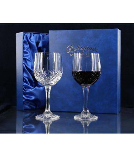 A pair of fully cut red wine goblets inside a dark blue satin lined presentation box.