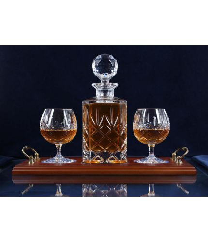 A 24% lead crystal fully cut square decanter and two brandy goblets on a serving tray. We can offer a personalised engraving on a engraved brass plate on the wooden tray with this set.