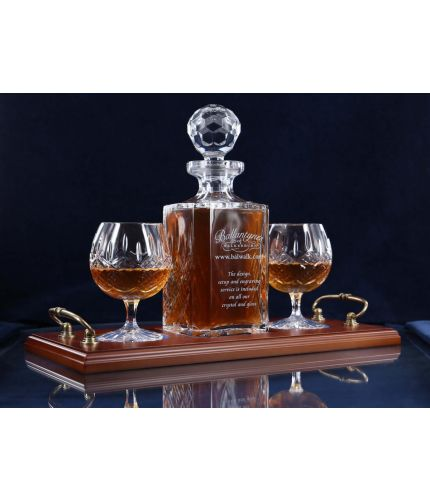 A 24% lead crystal panel cut square decanter and two full cut brandy goblets on a serving tray. We can offer a personalised engraving on the front of the decanter and an engraved brass plate on the wooden tray with this set.