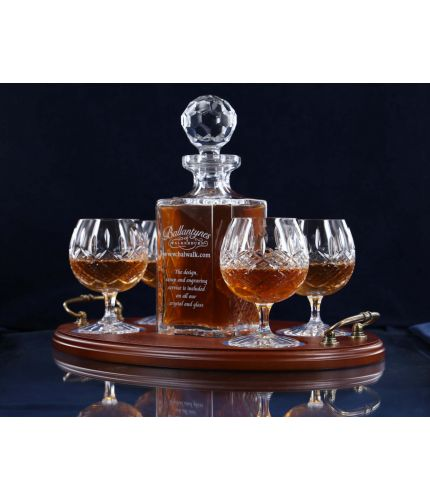 A 24% lead crystal panel cut square decanter and four fully cut brandy goblets on a serving tray. We can offer a personalised engraving on the front of the decanter and an engraved brass plate on the wooden tray with this set.