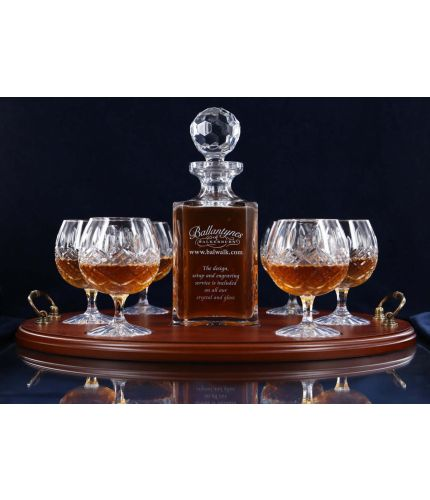 A 24% lead crystal panel cut square decanter and six fully cut brandy goblets on a serving tray. We can offer a personalised engraving on the front of the decanter and an engraved brass plate on the wooden tray with this set.