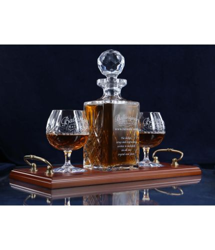 A 24% lead crystal panel cut square decanter and two panel cut brandy goblets on a serving tray. We can offer a personalised engraving on the front of the decanter, goblets and an engraved brass plate on the wooden tray with this set.