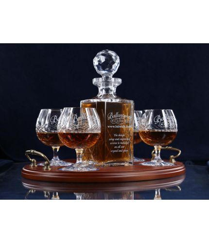 A 24% lead crystal panel cut square decanter and four panel cut brandy goblets on a serving tray. We can offer a personalised engraving on the front of the decanter, goblets and an engraved brass plate on the wooden tray with this set.