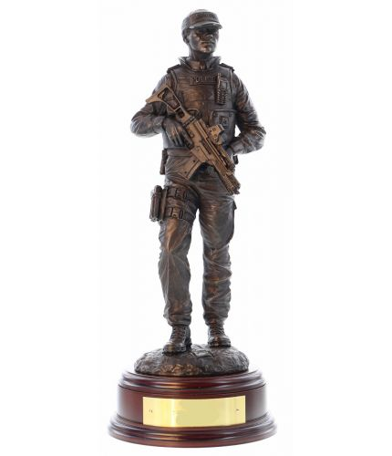 A hand made bronze cold cast resin statue of a Modern Male British Armed Police officer on foot patrol. In this sculpture he's wearing a police issue baseball cap. The sculpture is 12 Inches tall, we include the standard wooden base and an engraved brass